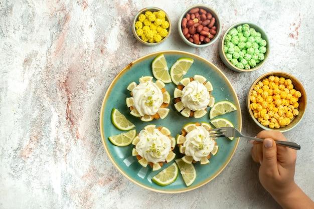 Vue de dessus de délicieux gâteaux crémeux avec des tranches de citron sur une surface blanche gâteau biscuit biscuit crème thé sucré