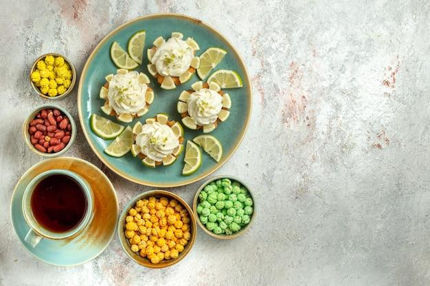 Vue de dessus de délicieux gâteaux crémeux avec des tranches de citron et une tasse de thé sur une surface blanche gâteau biscuit biscuit crème thé sucré