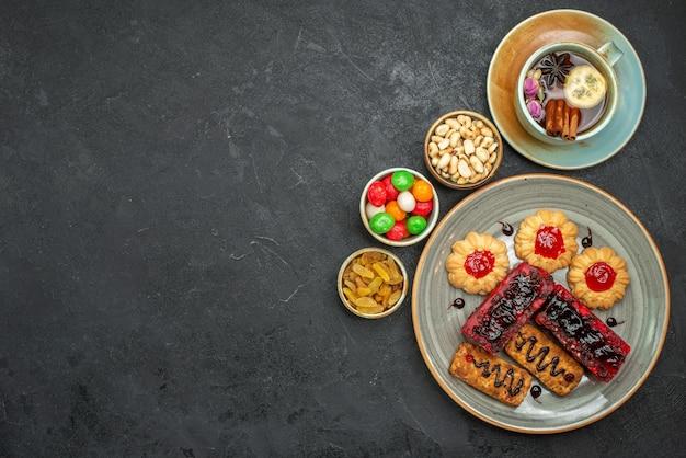 Vue de dessus de délicieux gâteaux fruités avec des biscuits et une tasse de thé dans l'obscurité