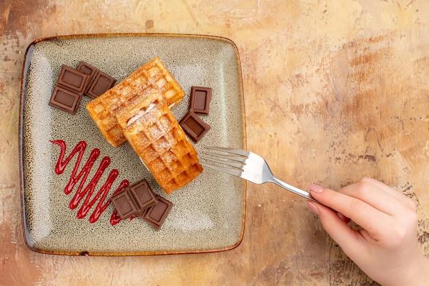 Vue de dessus de délicieux gâteaux gaufres avec des barres de chocolat sur un bureau marron