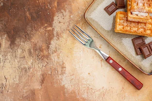Vue de dessus de délicieux gâteaux gaufres avec des barres de chocolat sur le fond marron