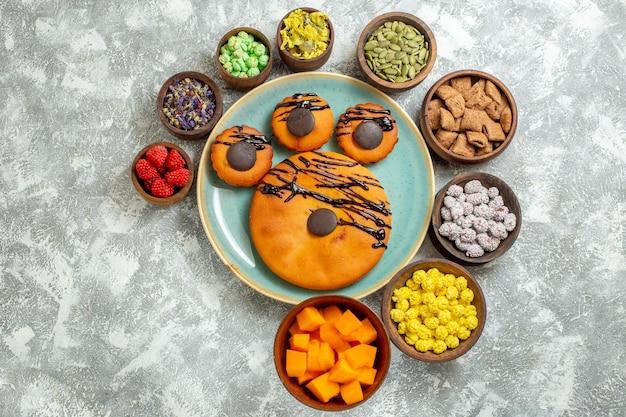 Vue de dessus de délicieux gâteaux avec glaçage au chocolat et bonbons sur surface blanche bonbons thé dessert biscuit biscuits gâteau