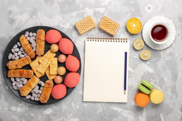 Vue de dessus de délicieux gâteaux avec des macarons de bagels et une tasse de thé sur une surface blanche grise
