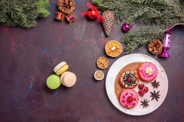 Vue de dessus de délicieux gâteaux avec des macarons français sur fond noir