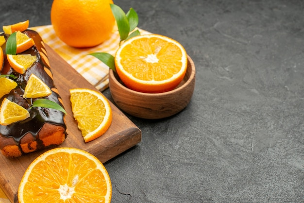 Vue de dessus de délicieux gâteaux mous entiers et citrons coupés avec des feuilles sur table sombre