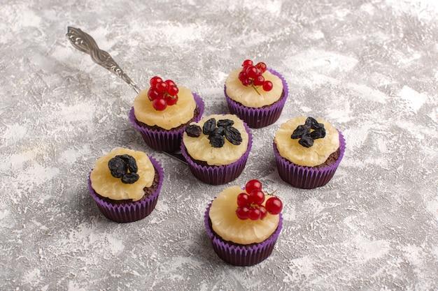 Vue de dessus de délicieux gâteaux ronds avec des fruits sur le dessus et sur le fond blanc gâteau bsicuti sucre pâte sucrée