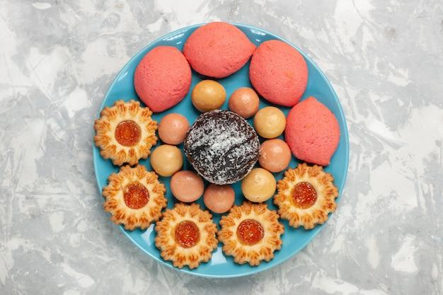 Vue de dessus de délicieux gâteaux roses avec des biscuits et un gâteau au chocolat sur une surface blanche