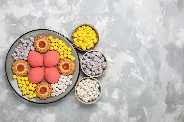 Vue de dessus de délicieux gâteaux roses avec des bonbons et des biscuits sur la surface blanche gâteau sucré biscuit tarte au thé cookies