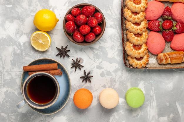 Vue de dessus de délicieux gâteaux roses avec macarons biscuits et thé sur une surface blanche