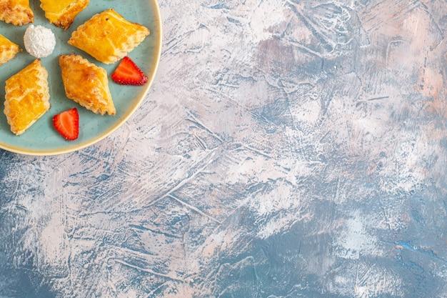 Vue de dessus de délicieux gâteaux sucrés aux fraises sur un bureau bleu