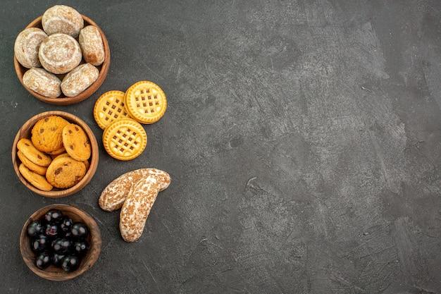 Vue de dessus de délicieux gâteaux sucrés avec des biscuits et des olives sur le gâteau sucré de tarte de surface sombre