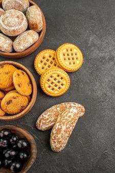 Vue de dessus de délicieux gâteaux sucrés avec des biscuits et des olives sur la surface sombre gâteau à tarte sucré