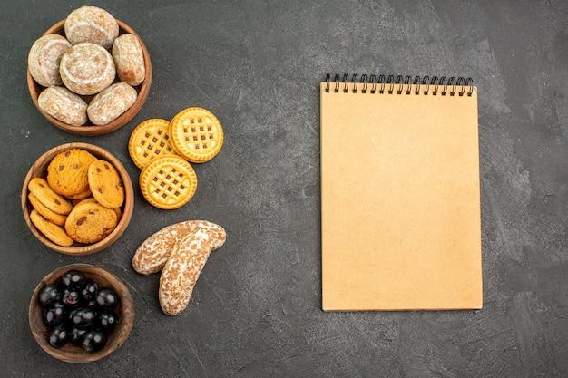 Vue de dessus de délicieux gâteaux sucrés avec des biscuits et des olives sur des tartes de surface sombre gâteau sucré