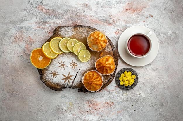 Vue de dessus de délicieux gâteaux sucrés avec des tranches de citron et une tasse de thé sur une surface blanche