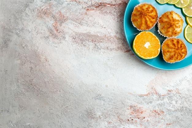 Vue de dessus de délicieux gâteaux avec des tranches de citron à l'intérieur de la plaque sur fond blanc gâteau aux agrumes fruits cuire la pâte de sucre biscuit