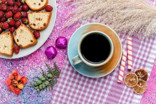 Vue de dessus de délicieux gâteaux en tranches avec une tasse de café et des fraises rouges sur le bureau rose clair
