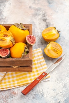 Vue de dessus de délicieux kakis et figues coupées dans une boîte en bois sur fond nude