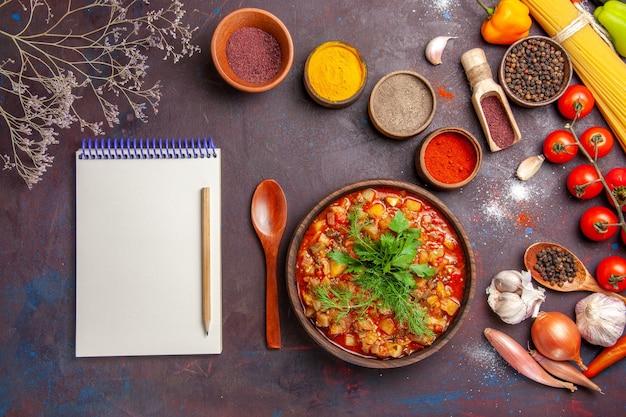 Vue de dessus de délicieux légumes cuits en tranches avec différents assaisonnements sur fond sombre sauce soupe nourriture repas légume