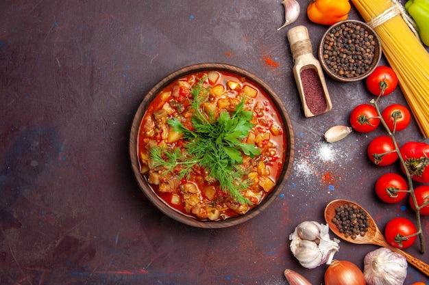 Vue de dessus de délicieux légumes cuits en tranches avec des légumes verts et des assaisonnements sur le fond sombre sauce soupe repas nourriture