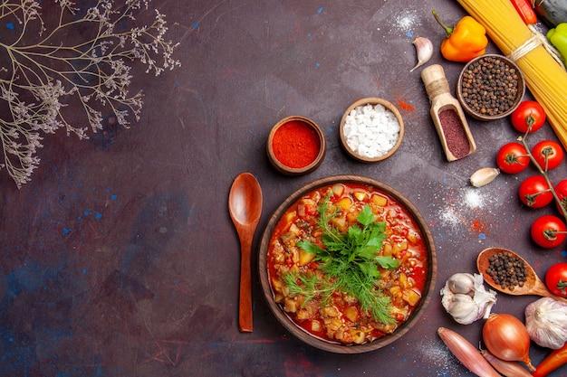 Vue de dessus de délicieux légumes cuits tranchés avec des légumes verts et des assaisonnements sur le fond sombre de la soupe de nourriture de repas de la sauce