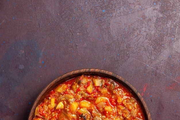 Vue de dessus de délicieux légumes cuits tranchés avec de la sauce sur un bureau sombre sauce alimentaire soupe repas légumes