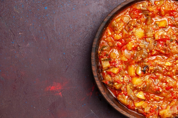 Vue de dessus de délicieux légumes cuits tranchés avec sauce sur fond sombre sauce alimentaire soupe repas légume