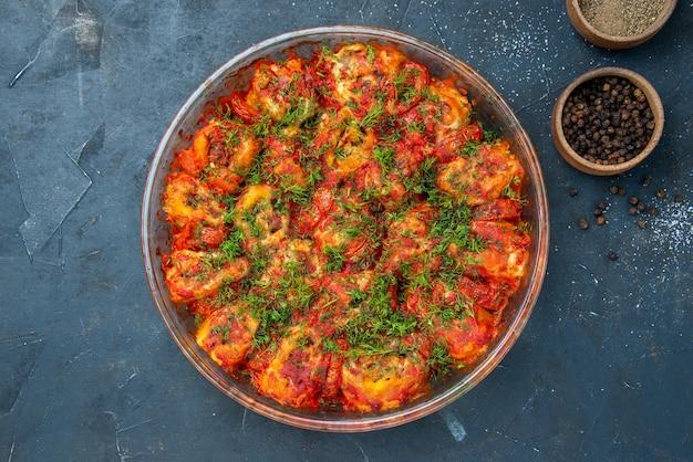 Vue de dessus de délicieux légumes cuits avec de la viande hachée et des légumes verts à l'intérieur de la casserole sur un plat de table bleu repas viande cuisine nourriture famille goût