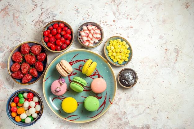 Vue de dessus de délicieux macarons français avec des baies et des bonbons sur un gâteau blanc biscuit sucré
