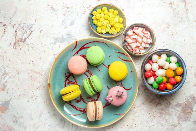 Vue de dessus de délicieux macarons français avec des bonbons sur un biscuit de gâteau blanc