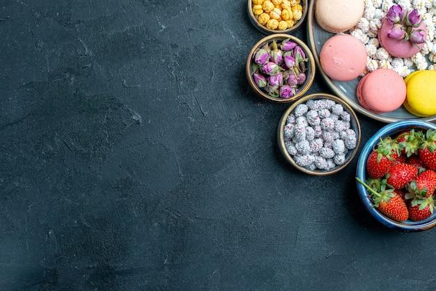 Vue de dessus de délicieux macarons français avec des bonbons et des fruits sur un sol gris