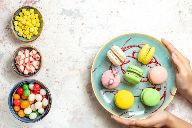 Vue de dessus de délicieux macarons français avec des bonbons sur un gâteau blanc biscuit sucré
