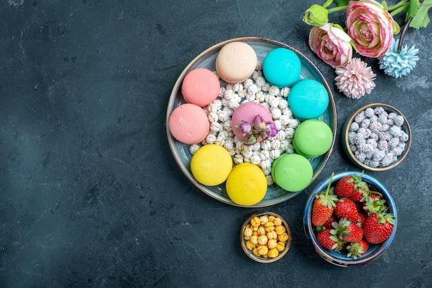 Vue de dessus de délicieux macarons français avec des bonbons à l'intérieur du plateau sur l'espace sombre
