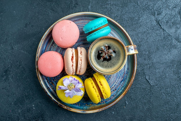 Vue de dessus de délicieux macarons français sur un espace sombre