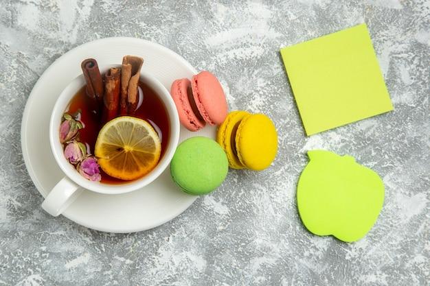 Vue de dessus de délicieux macarons français gâteaux colorés avec du thé sur une surface blanche
