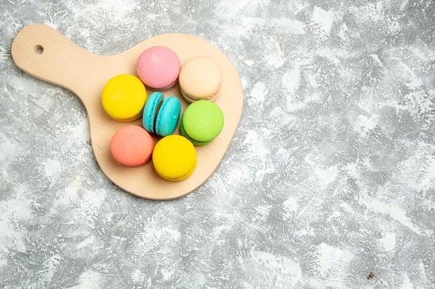 Vue de dessus de délicieux macarons français gâteaux colorés sur une surface blanche