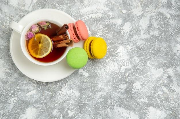 Vue de dessus de délicieux macarons français gâteaux colorés avec une tasse de thé sur une surface blanche