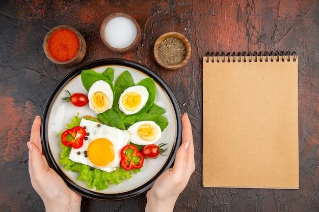 Vue de dessus de délicieux œufs brouillés avec salade et tomates sur table sombre