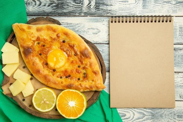 Vue de dessus délicieux pain aux œufs cuit au four avec du fromage sur un bureau gris rustique