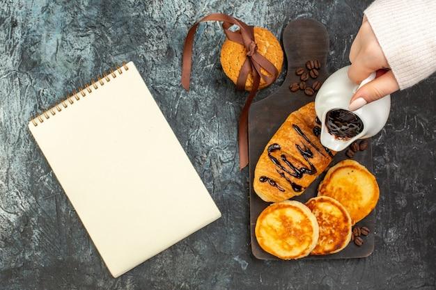 Vue de dessus d'un délicieux petit-déjeuner avec des crêpes et des biscuits empilés croissants et un cahier sur une surface sombre