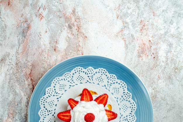 Vue de dessus délicieux petit gâteau à la crème et aux fraises sur un espace blanc