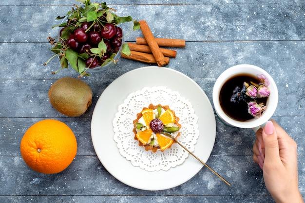 Une vue de dessus délicieux petit gâteau avec de la crème et des fruits frais en tranches avec du thé à la cannelle sur le bureau gris-bleu biscuit aux fruits