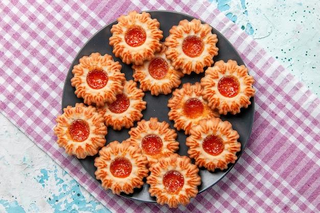 Vue de dessus de délicieux petits cookies avec de la confiture d'orange sur le bureau bleu biscuit biscuit thé sucré couleur sucre