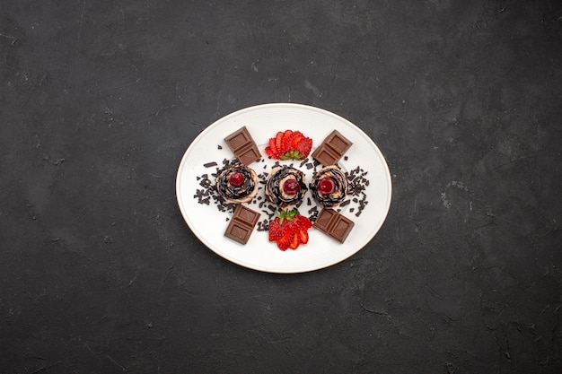 Vue de dessus de délicieux petits gâteaux avec des barres de chocolat et des fraises sur fond sombre tarte au gâteau au cacao thé sucré