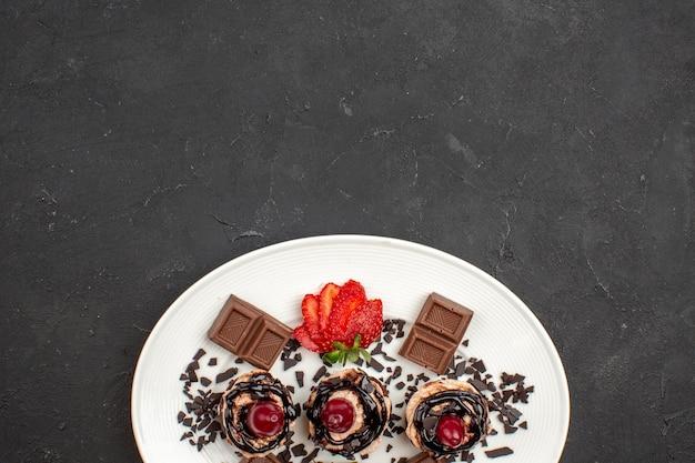 Vue de dessus de délicieux petits gâteaux avec des barres de chocolat et des fraises sur fond sombre tarte gâteau au chocolat et au cacao thé sucré