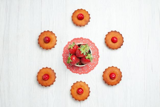 Vue de dessus de délicieux petits gâteaux sur un bureau blanc