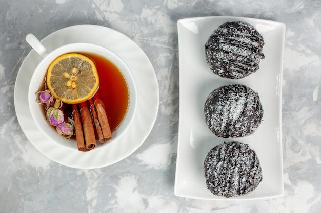 Vue de dessus de délicieux petits gâteaux avec glaçage à la cannelle et tasse de thé sur la surface blanche du gâteau biscuit au thé cuire la tarte sucrée au sucre