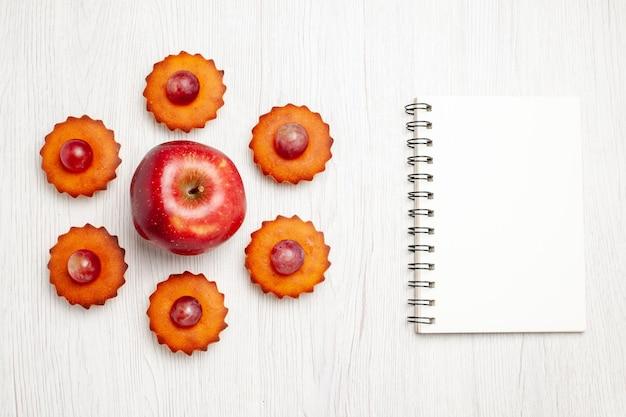 Vue de dessus de délicieux petits gâteaux avec des pommes fraîches sur une surface blanche dessert biscuit thé gâteau tarte biscuits