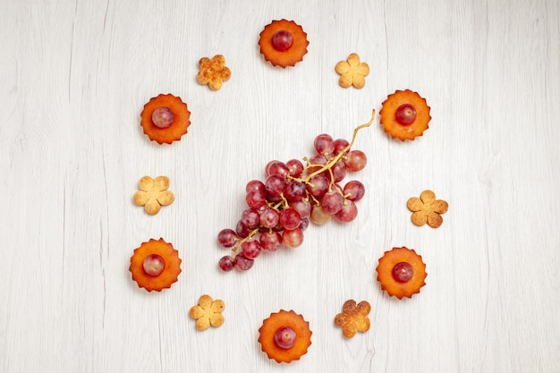 Vue de dessus de délicieux petits gâteaux avec des raisins et des biscuits sur une surface blanche dessert thé aux fruits biscuit biscuit tarte au gâteau