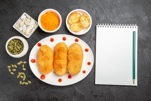 Vue de dessus de délicieux petits pains aux pommes de terre avec des ingrédients sur le fond gris foncé