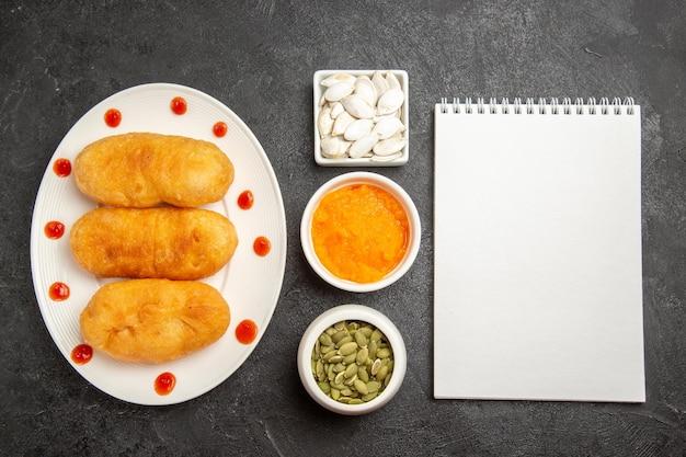 Vue de dessus de délicieux petits pains cuits au four avec bloc-notes sur une surface grise